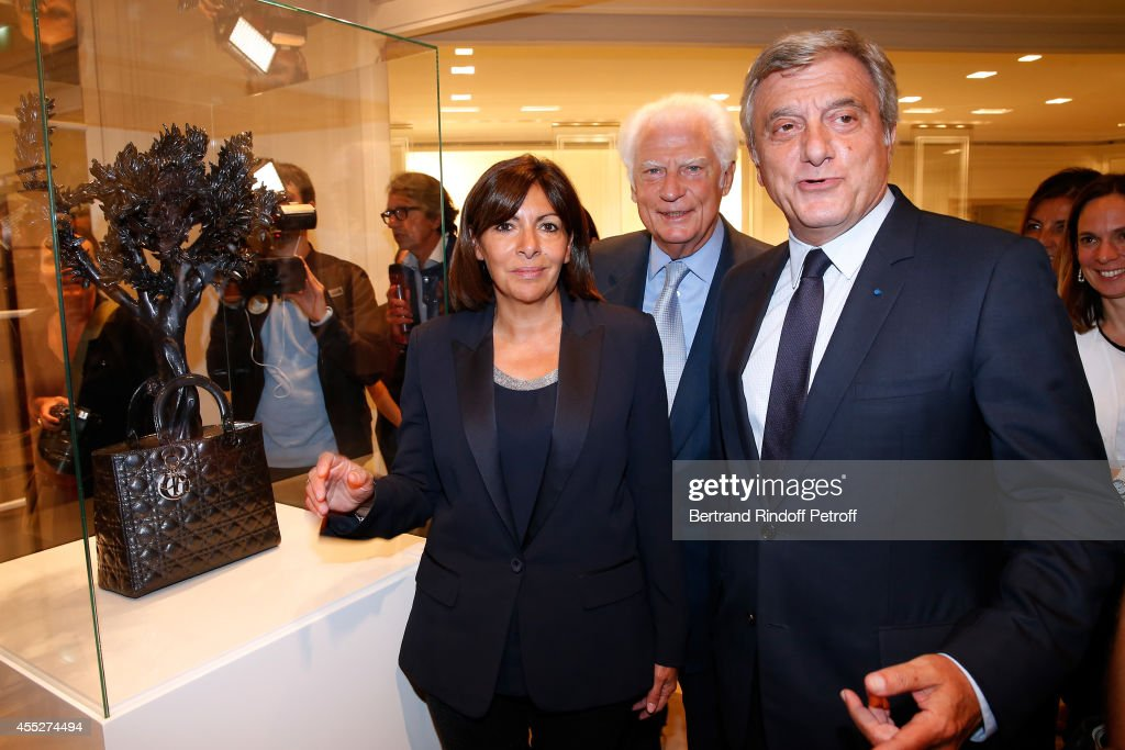Mayor of Paris Anne Hidalgo, CEO Comite Montaigne Jean Claude Cathalan and CEO Dior Sidney Toledano pose front of the work from Tayfun Serttas, Lady dream (2012, Polyester) during the 'Promenade pour un objet d'exception'. Held at Boutique Dior Montaigne on September 11, 2014 in Paris, France.