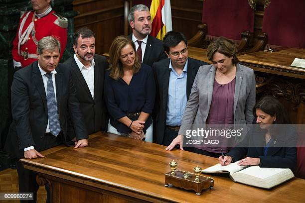 Mayor of Paris Anne Hidalgo signs on the Book of Honor beside the Mayor of Barcelona Ada Colau and other city hall resentatives following the signing...