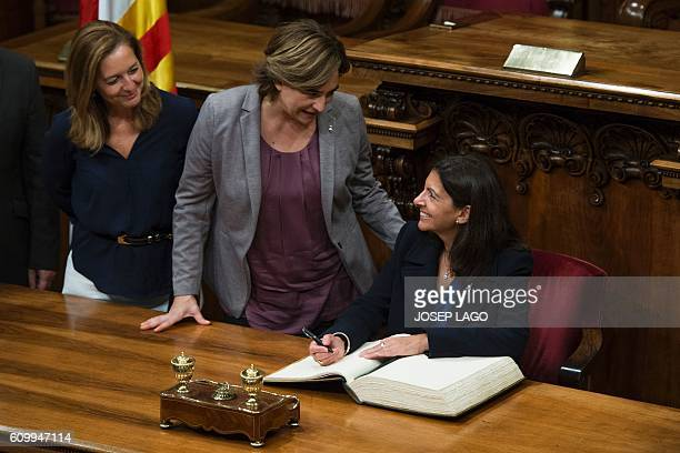 Mayor of Paris Anne Hidalgo smiles at Mayor of Barcelona Ada Colau as she signs on the Book of Honor following the signing of a collaboration...