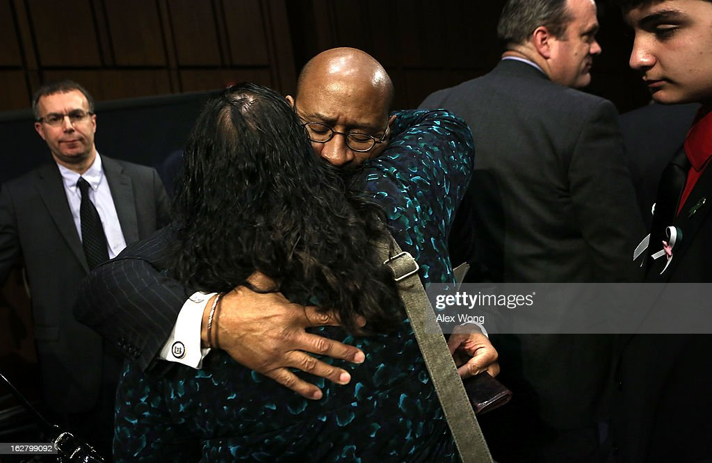 Mayor of Philadelphia and president of the U.S. Conference of Mayors <a gi-track='captionPersonalityLinkClicked' href=/galleries/search?phrase=Michael+Nutter&family=editorial&specificpeople=4695146 ng-click='$event.stopPropagation()'>Michael Nutter</a> (3rd L) hugs Donna Soto (2nd L), mother of Sandy Hook Elementary shooting victim first-grade teacher Victoria Soto, as Victoria's brother Carlos M. Soto (R) looks on during a hearing before the Senate Judiciary Committee February 27, 2013 on Capitol Hill in Washington, DC. The committee held a hearing on 'The Assault Weapons Ban of 2013.'