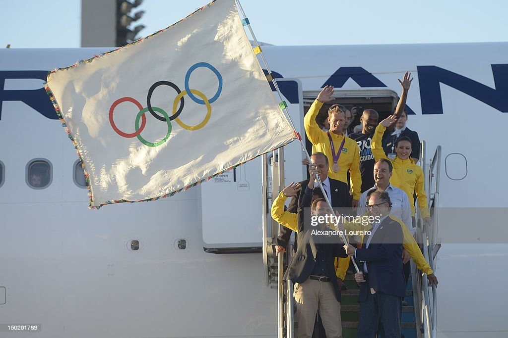 Mayor of Rio de Janeiro, Eduardo Paes, President of Rio 2016 Commite, Carlos Arthur Nuzman, Governor of Rio de Janeiro, Sergio Cabral Filho and atlhetes of brasil arrive at the international airport of Rio de Janeiro with the Olympic flag on August 13, 2012 in Rio de Janeiro, Brazil.