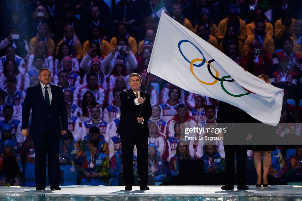 Mayor of Sochi Anatoly Pakhomov (L) and Mayor of Pyeongchang Lee Seok-rae (R) look on as President of the International Olympic Committee (IOC) Thomas Bach (C) waves the Olympic flag during the 2014 Sochi Winter Olympics Closing Ceremony at Fisht Olympic Stadium on February 23, 2014 in Sochi, Russia.