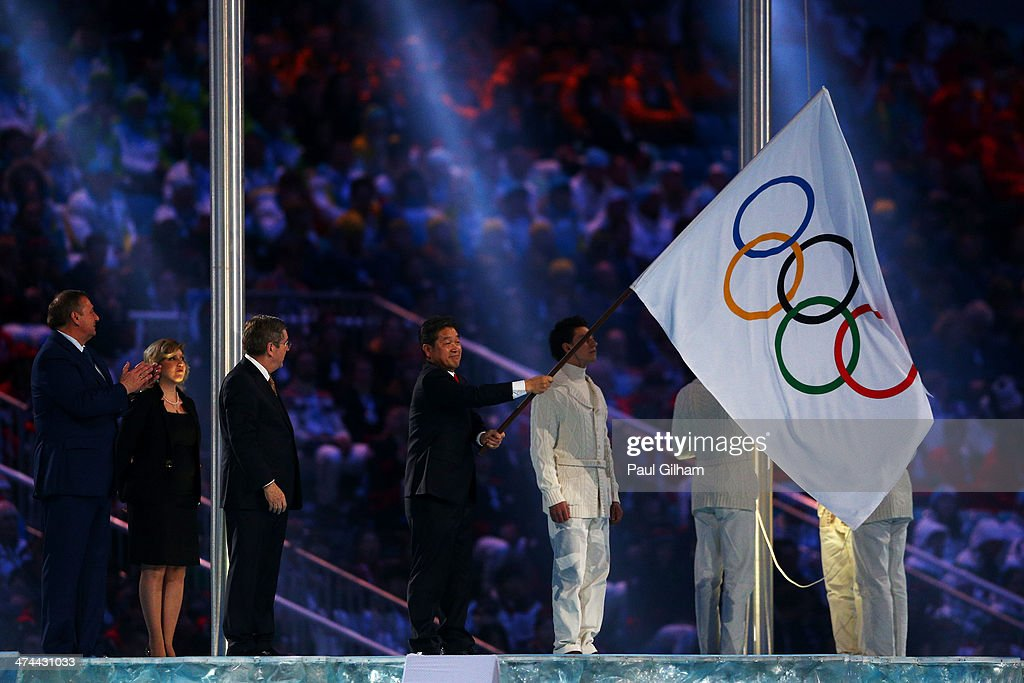 Mayor of Sochi Anatoly Pakhomov and President of the International Olympic Committee (IOC) Thomas Bach look on as Mayor of Pyeongchang Lee Seok-rae waves the Olympic flag during the 2014 Sochi Winter Olympics Closing Ceremony at Fisht Olympic Stadium on February 23, 2014 in Sochi, Russia.