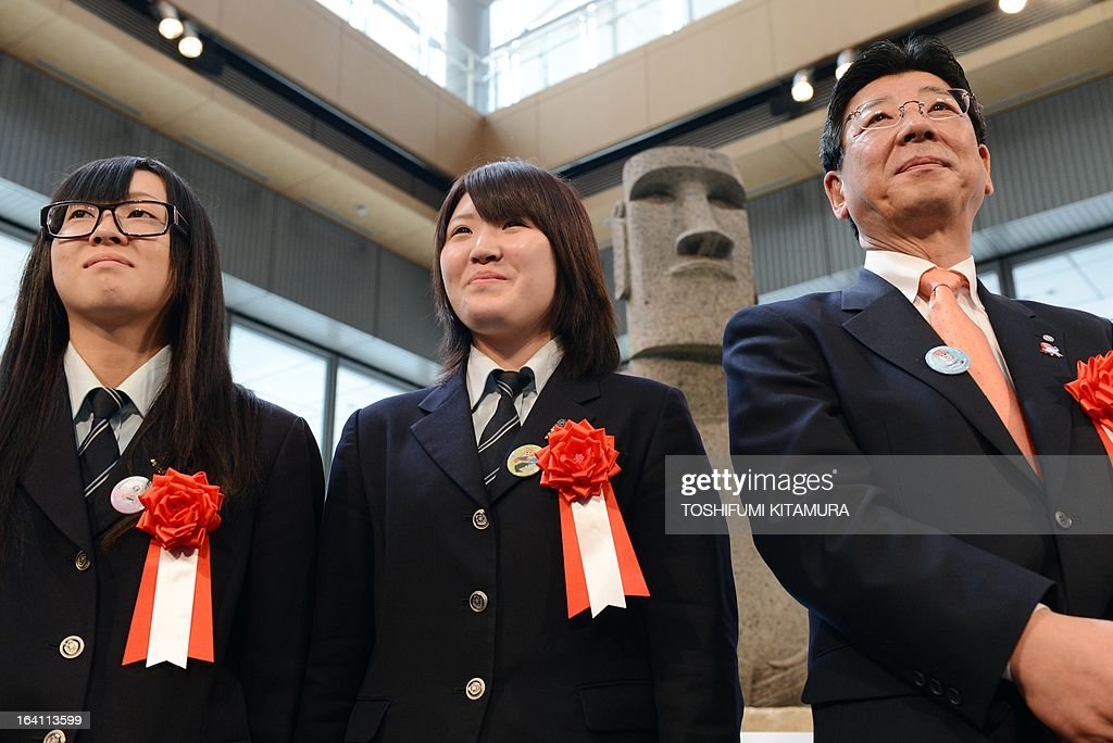Mayor of the tsunami-devastated town of Minamisanriku, Jin Sato (R) and students from Minamisanriku's Sizugawa high school, Nana Yamauchi (L) and Chie Shuto (C) pose during a photo session in front of the new 'Moai' statue (back centre R), modelled on the mysterious carvings at Easter Island, during its preview in Tokyo on March 20, 2013. The giant present crossed the ocean from Chile as the town's original was destroyed in the March 11 quake-sparked tsunami disaster in 2011. AFP PHOTO / TOSHIFUMI KITAMURA