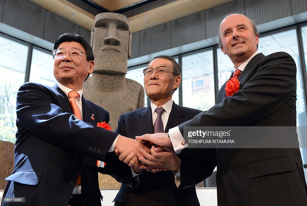 Mayor of the tsunami-devastated town of Minamisanriku, Jin Sato, Japan-Chile Economic Committee chairman Mikio Sasaki (C) and Chilean Ambassador to Japan Patricio Torres join hands in front of the new 'Moai' statue (back), modelled on the mysterious carvings at Easter Island, during its preview in Tokyo on March 20, 2013. The giant present crossed the ocean from Chile as the town's original was destroyed in the March 11 quake-sparked tsunami disaster in 2011.