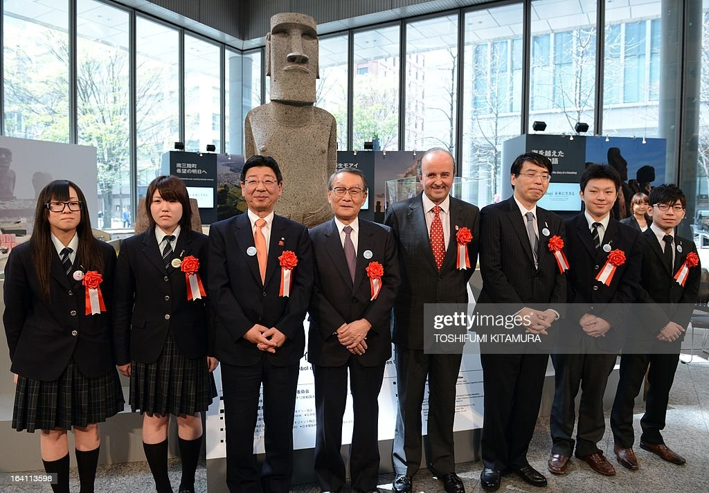 Mayor of the tsunami-devastated town of Minamisanriku, Jin Sato (3rd L), Japan-Chile Economic Committee chairman, Mikio Sasaki (4th L), Chilean Ambassador to Japan, Patricio Torres (4th R) and Akira Yamada of foreign ministry (3rd R) pose during a photo session in front of the new 'Moai' statue (back C), modelled on the mysterious carvings at Easter Island, with students and workers from Minamisanriku's Sizugawa high school during its preview in Tokyo on March 20, 2013. The giant present crossed the ocean from Chile as the town's original was destroyed in the March 11 quake-sparked tsunami disaster in 2011. AFP PHOTO / TOSHIFUMI KITAMURA