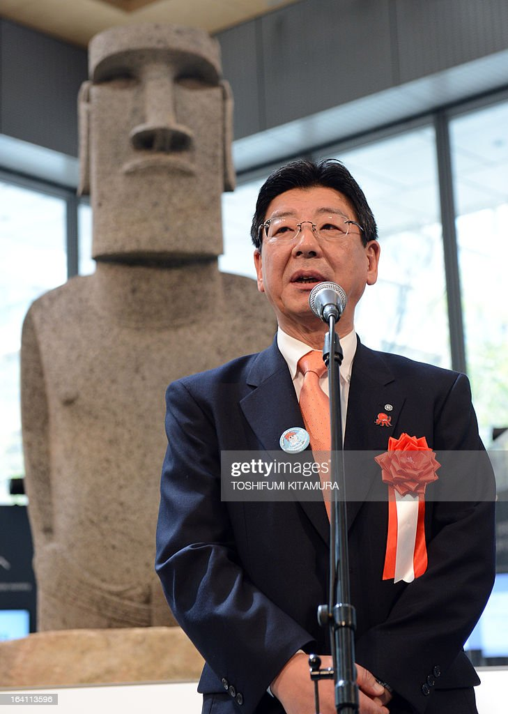 Mayor of the tsunami-devastated town of Minamisanriku, Jin Sato speaks in front of the new 'Moai' statue, modelled on the mysterious carvings at Easter Island, during its preview in Tokyo on March 20, 2013. The giant present crossed the ocean from Chile as the town's original was destroyed in the March 11 quake-sparked tsunami disaster in 2011. AFP PHOTO / TOSHIFUMI KITAMURA