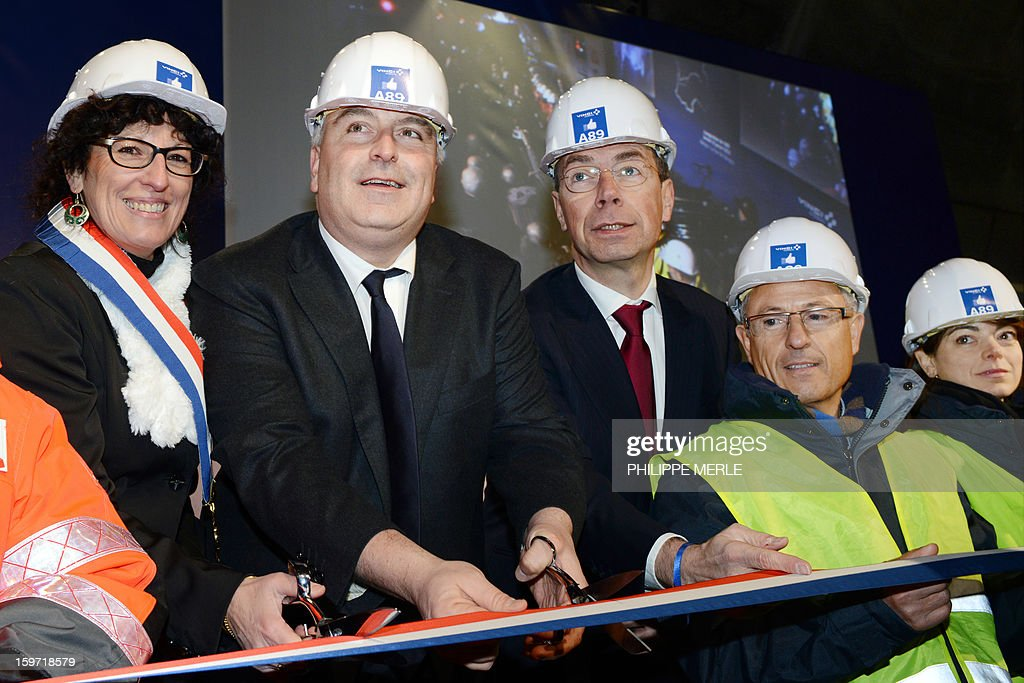 Mayor of Violay Veronique Chaverot (L), French minister for Transports and Maritime Economy Frederic Cuvillier (2L) and President of Vinci Motorways Pierre Copey cut the ribbon on January 19, 2013 during the inauguration ceremony for the openning of the first section of the A89 tollway, in Balbigny, France's Loire valley. The new route is the first transversal highway across France and links Bordeaux to Lyon. AFP PHOTO PHILIPPE MERLE