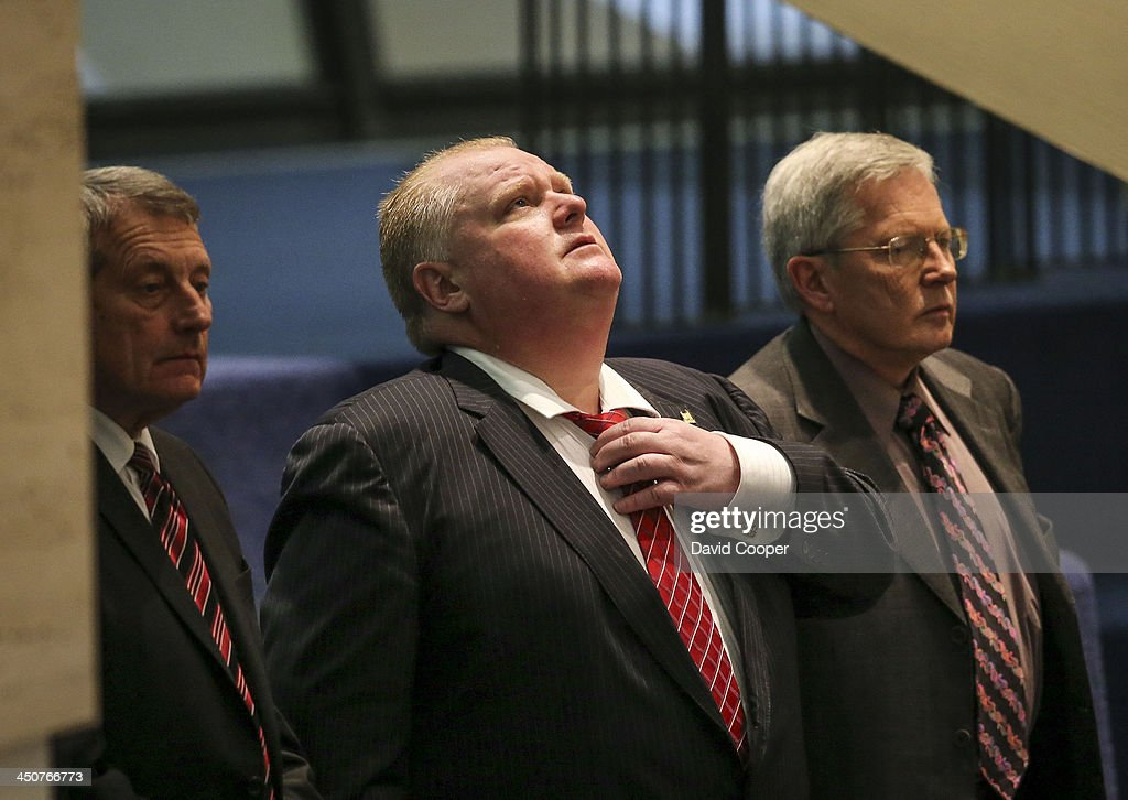 Mayor Rob Ford loosens his tie and looks skyward as he stands in the gallery with his legal team, lawyers Dennis Morris (left) and George Rust D'Eye (right) before the meeting as council debates the motion to limit the Mayors office budget November 18, 2013.