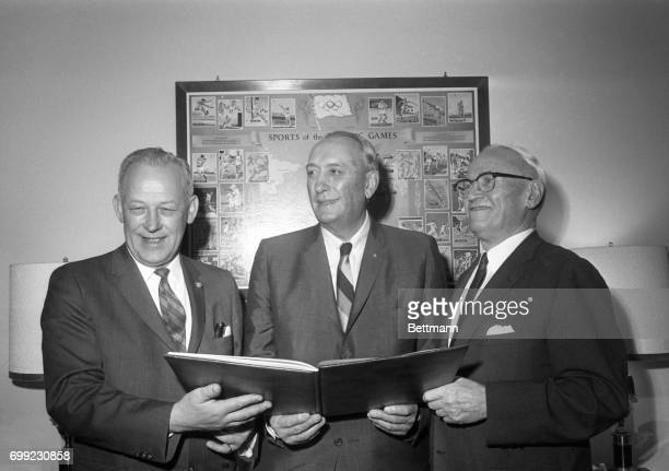 mayor Terry Schrunk and Pacific Power and Light Co Board Charmian Paul B McKee show US Olympic Committee President Kenneth Wilson why they think...