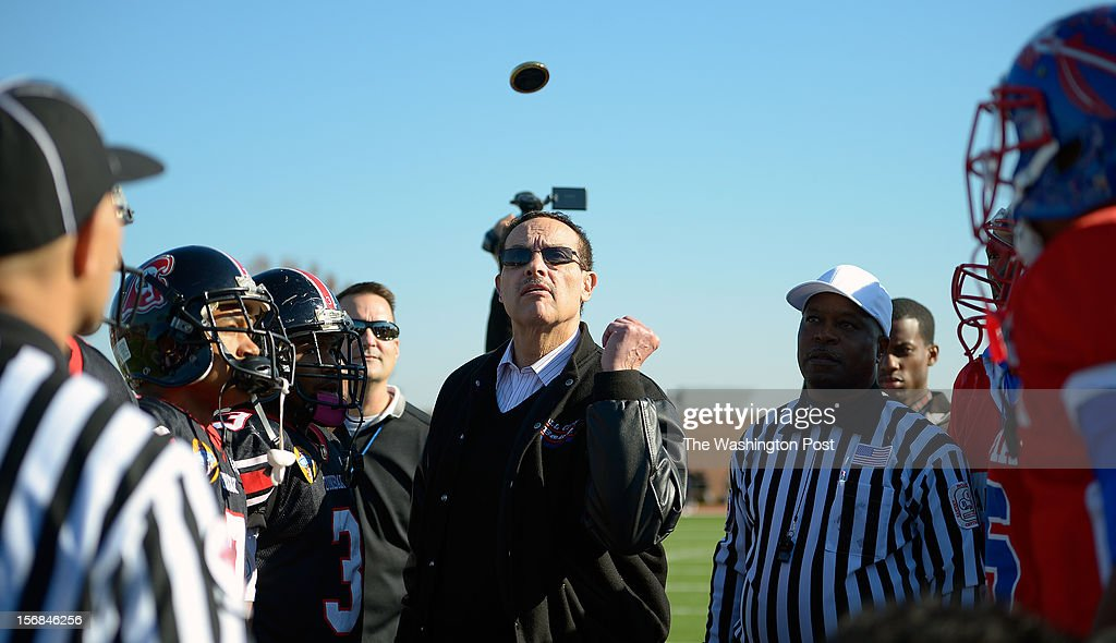 DC Mayor Vincent Gray tosses the coin to determine who with kick off before Dunbar defeated Anacostia 12 - 8 in the Turkey Bowl at Eastern High School in Washington DC, November 22, 2012 .