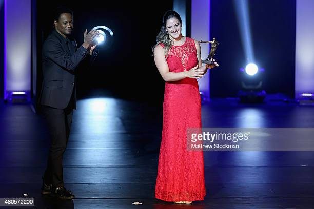 Mayra Aguiar poses with her Judo Athlete of the Year Trophy as Toni Garrido looks on during the Brazil Olympics Awards Ceremony at Theatro Municipal...