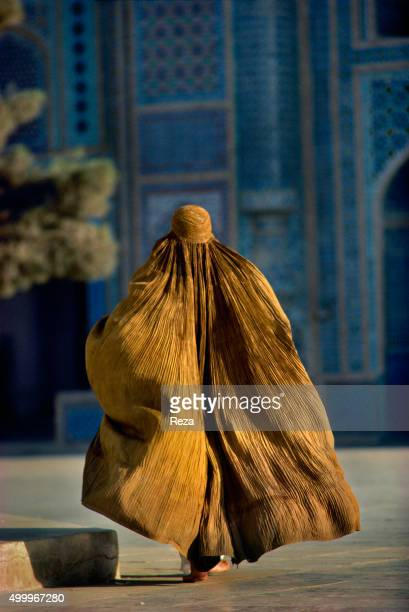 1990 Mazare Sharif Afghanistan A woman clad in a burqa by the mosque in the wee hours of the morning The town of MazareSharif in Afghanistan is the...