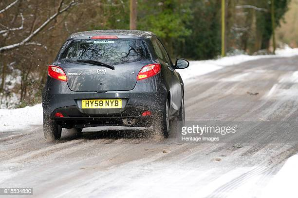 Mazda 2 driving on snowy road Artist Unknown