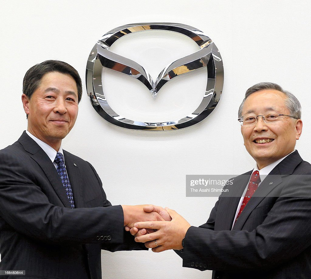 Mazda Motor Co incoming president and CEO Masamichi Kogai (L) and president Takashi Yamanouchi shake hands during a press conference on May 9, 2013 in Tokyo, Japan. Current President Takashi Yamanouchi will step down next month.