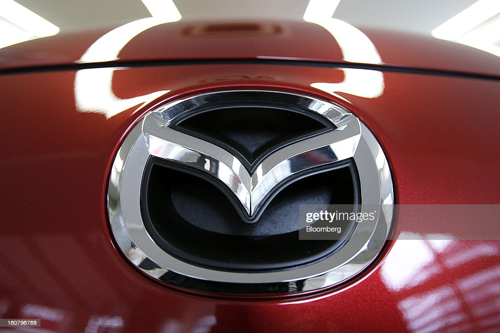 A Mazda Motor Corp. badge is displayed on the front of a Premacy minivan, known as the Mazda 5 outside of Japan, at the company's showroom in Tokyo, Japan, on Wednesday, Feb. 6, 2013. Mazda, the best performer on the Nikkei 225 Stock Average in the past three months, more than doubled its full-year profit forecast on a weaker yen and demand for its fuel-efficient vehicles. Photographer: Kiyoshi Ota/Bloomberg via Getty Images