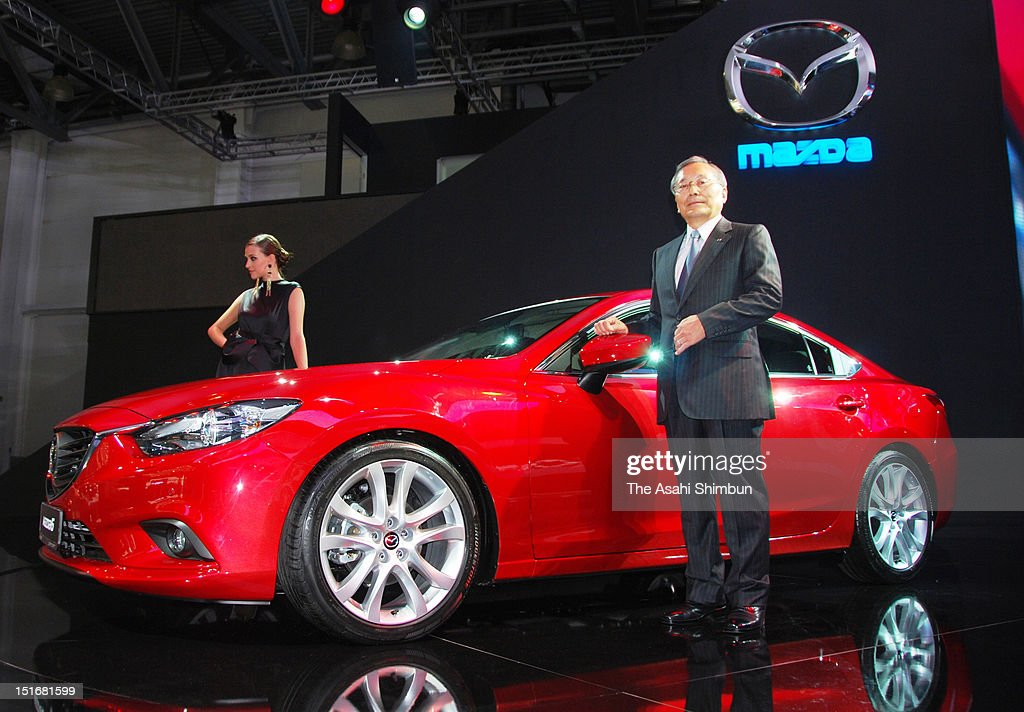 Mazda Motor Corporation CEO and President <a gi-track='captionPersonalityLinkClicked' href=/galleries/search?phrase=Takashi+Yamanouchi&family=editorial&specificpeople=5292471 ng-click='$event.stopPropagation()'>Takashi Yamanouchi</a> poses for photographs with their new model 'Mazda 6' during the Moscow International Motor Show on August 29, 2012 in Moscow, Russia. Yamanouchi sees Russia as one of the most promising markets.