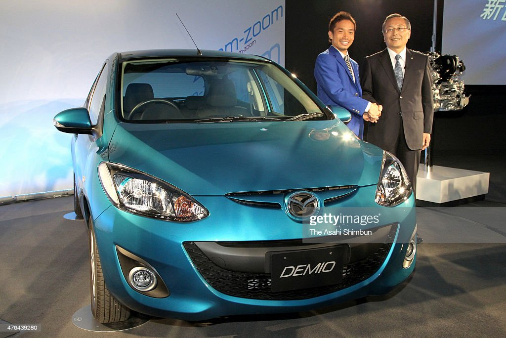 Mazda Motor Co's President Takashi Yamauchi (R) and football player <a gi-track='captionPersonalityLinkClicked' href=/galleries/search?phrase=Yuto+Nagatomo&family=editorial&specificpeople=4320811 ng-click='$event.stopPropagation()'>Yuto Nagatomo</a> shake hands next to the new Demio during the unveiling on June 9, 2011 in Fuchu, Hiroshima, Japan.