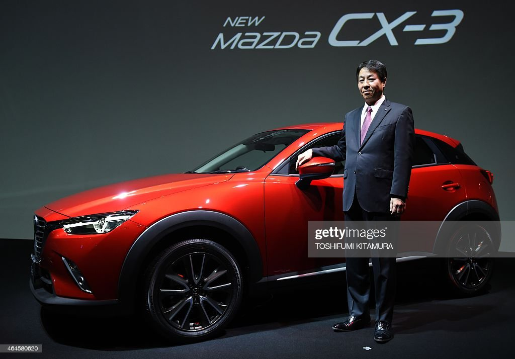Mazda motors president and CEO <a gi-track='captionPersonalityLinkClicked' href=/galleries/search?phrase=Masamichi+Kogai&family=editorial&specificpeople=10904432 ng-click='$event.stopPropagation()'>Masamichi Kogai</a> stands beside the company's new compact crossover SUV, 'Mazda CX-3' during its press preview in Tokyo on February 27, 2015. Mazda started to put the SKYACTIV-D1.5 clean diesel engine-equipped CX-3 on the Japanese market from February 27.