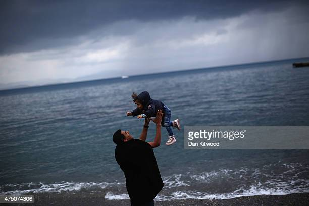 Mazen from Syria throws his daughter Bissan in the air while standing on the beach outside the police station on May 29 2015 in Kos Greece Migrant...