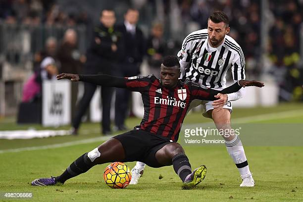 Mbaye Niang of AC Milan is tackled by Andrea Barzagli of Juventus FC during the Serie A match between Juventus FC and AC Milan at Juventus Arena on...