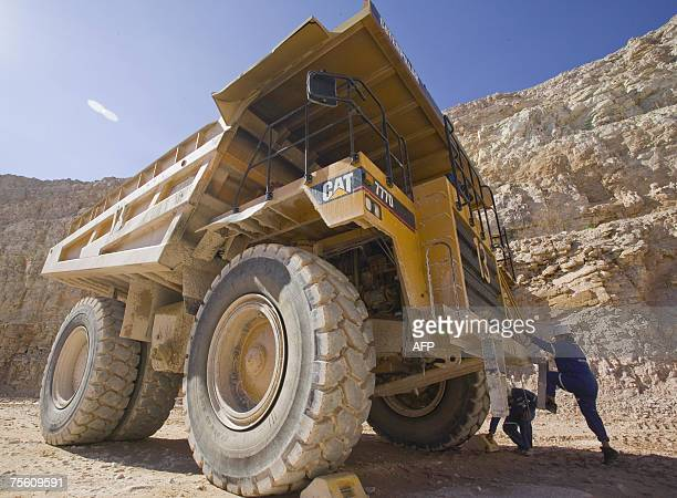 The only female driver of a onehundred ton Caterpillar truck Marie Jone climbs into the cab of her truck at the Sue E open pit uranium mine at Areva...