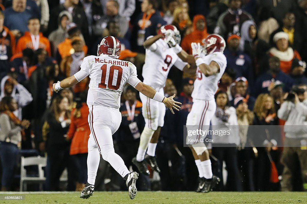AJ McCarron #10 celebrates throwing a 99 yard touchdown reception to <a gi-track='captionPersonalityLinkClicked' href=/galleries/search?phrase=Amari+Cooper&family=editorial&specificpeople=8797589 ng-click='$event.stopPropagation()'>Amari Cooper</a> #9 of the Alabama Crimson Tide in the fourth quarter against the Auburn Tigers at Jordan-Hare Stadium on November 30, 2013 in Auburn, Alabama.