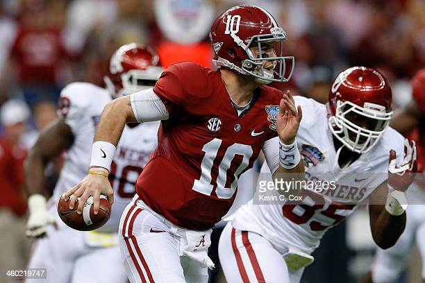 McCarron of the Alabama Crimson Tide runs with the ball past Geneo Grissom of the Oklahoma Sooners during the Allstate Sugar Bowl at the MercedesBenz...