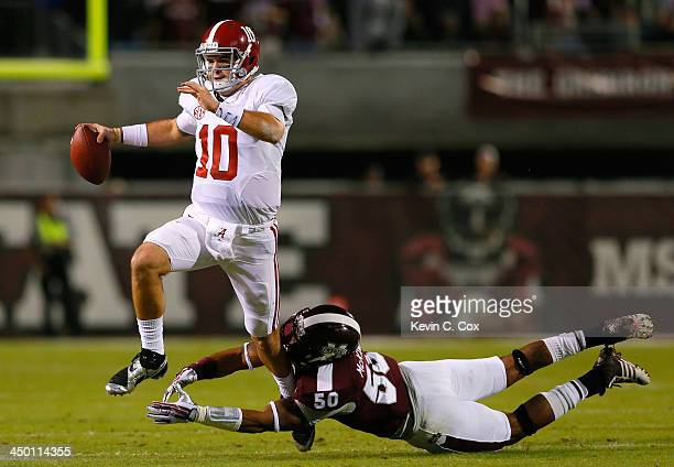 McCarron of the Alabama Crimson Tide rushes away from a tackle by Benardrick McKinney of the Mississippi State Bulldogs at Davis Wade Stadium on...
