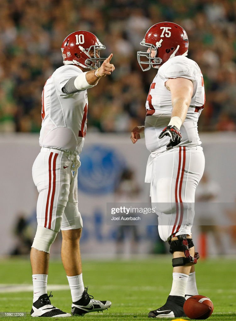 AJ McCarron #10 of the Alabama Crimson Tide talks to teammate Barrett Jones #75 prior to taking a snap against the Notre Dame Fighting Irish during the 2013 Discover BCS National Championship Game at Sun Life Stadium on January 7, 2013 in Miami Gardens, Florida. Alabama defeated Notre Dame 42-14.