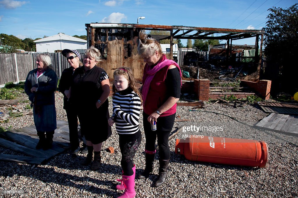 McCarthy sisters and family stand defiantly beside a burned out building at Dale Farm site prior to eviction Riot police and bailiffs were present on...