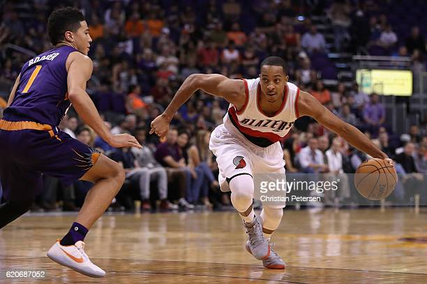 J McCollum of the Portland Trail Blazers drives the ball past Devin Booker of the Phoenix Suns during the first half of the NBA game at Talking Stick...