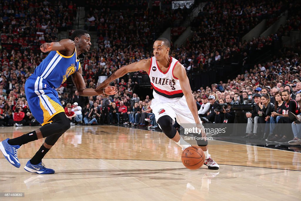 J McCollum of the Portland Trail Blazers drives to the basket Justin Holiday of the Golden State Warriors on March 24 2015 at the Moda Center in...