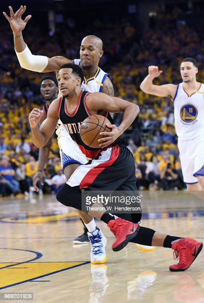 McCollum of the Portland Trail Blazers drives to the basket on David West of the Golden State Warriors in the fourth quarter during Game One of the...