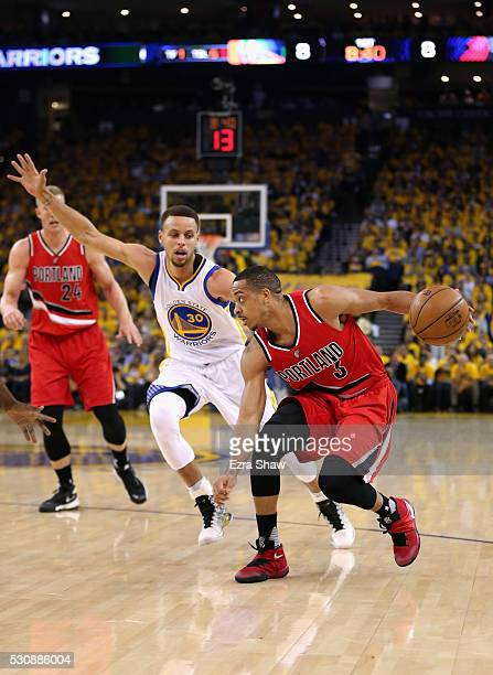 J McCollum of the Portland Trail Blazers is guarded by Stephen Curry of the Golden State Warriors during Game Five of the Western Conference...