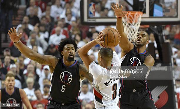 J McCollum of the Portland Trail Blazers is pressured by DeAndre Jordan and Chris Paul of the Los Angeles Clippers in the first quarter of Game Four...