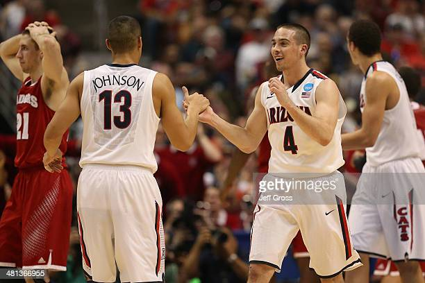 J McConnell and Nick Johnson of the Arizona Wildcats celebrate in the first half while taking on the Wisconsin Badgers during the West Regional Final...