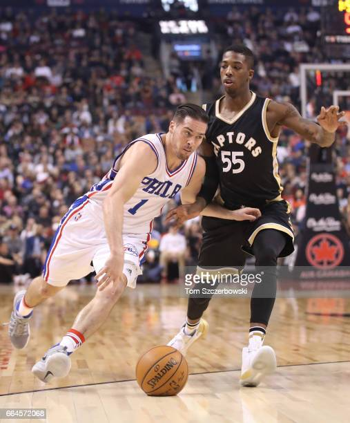 J McConnell of the Philadelphia 76ers dribbles as Delon Wright of the Toronto Raptors plays defense during NBA game action at Air Canada Centre on...