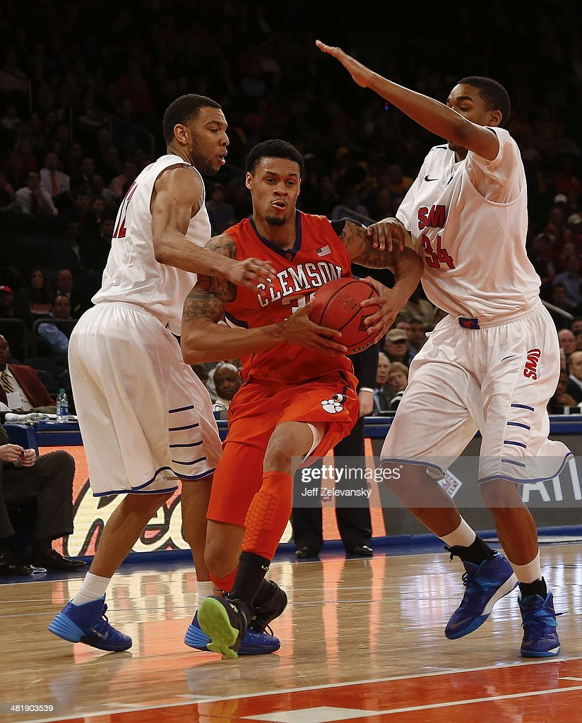 K.J. McDaniels #32 of the Clemson Tigers drives by Ben Moore #34 of the Southern Methodist Mustangs during the NIT Championship semifinals at Madison Square Garden on April 1, 2014 in New York City.