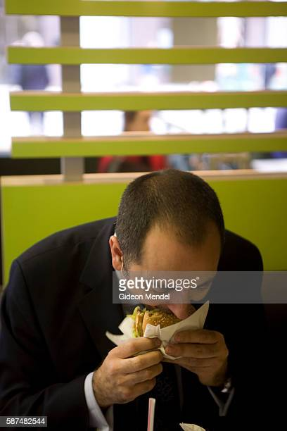 A McDonald's customer enthusiastically tucks into his Big Mac oblivious to the new trendy coffee bar style ambience and design at the Cannon Street...