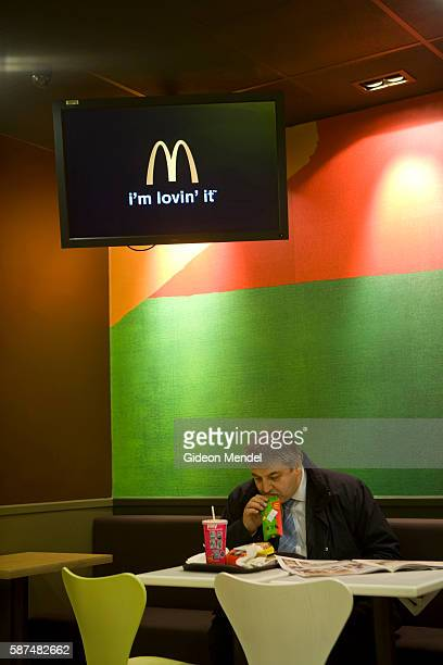 A McDonalds customer tucks into his fast food meal oblivious to the new trendy coffee bar style ambience and design at the Cannon Street branch of...