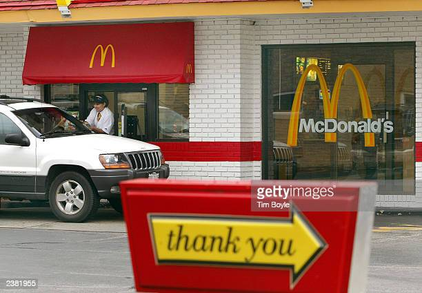 McDonald's employee assists a customer at its driveup window August 8 2003 in Chicago Illinois Oak Brook Illinoisbased McDonald's Corporation...