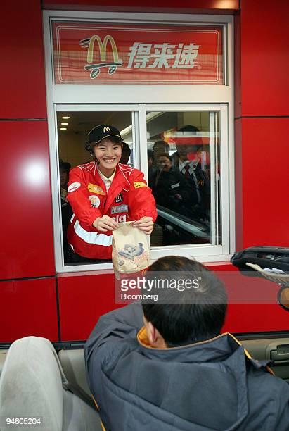 McDonald's employee hands a customer his order at the grand opening of a new outlet featuring a drivethrough in Shahe China near Beijing on Friday...