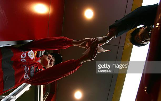 McDonald's employee hands food to a customer at a new McDonald's drivethru facility on January 19 2007 in Beijing China McDonald's opened its first...