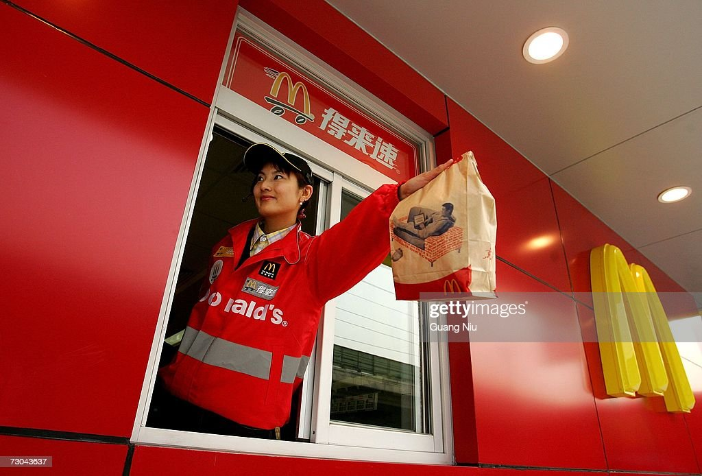 A McDonald's employee hands out food as she waits on customers at their new drive-thru facility on January 19, 2007 in Beijing, China. McDonald's opened its first restaurant in mainland China in 1990, in Shenzhen, Guangdong province and now operates 760 restaurants countrywide, which employ over 50,000 people.