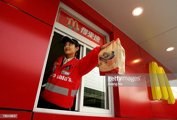 McDonald's employee hands out food as she waits on customers at their new drivethru facility on January 19 2007 in Beijing China McDonald's opened...