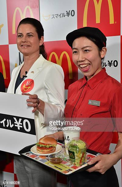 McDonald's Japan president Sarah Casanova and an employee displaysthe new menu 'Vegetable Chicken Burger' as the company announce the new business...