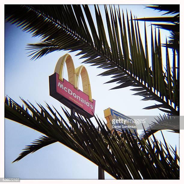 McDonald's logo and blockbuster logo seen through a palm tree