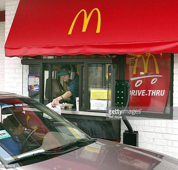 McDonald's worker delivers an order to a drivethru customer December 8 2003 at a McDonald's fastfood restaurant in Chicago Oak Brook Illinoisbased...