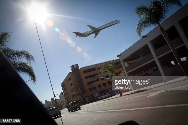A McDonnell Douglas MD90 of Delta Air Lines approaching San Diego International Airport flying low over a street and a parking garage